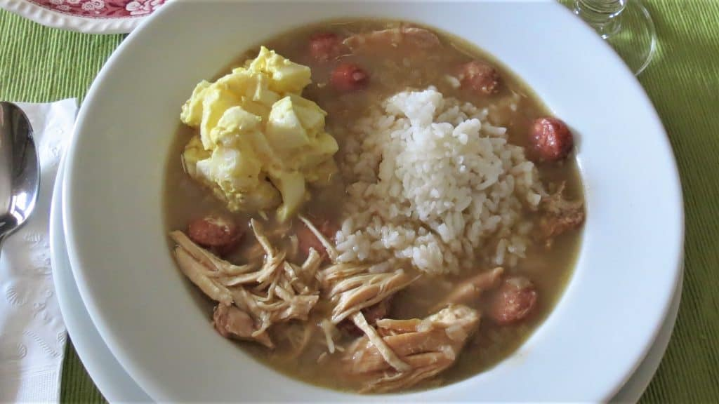 Bowl of Chicken Gumbo with a scoop of rice and potato salad in it.