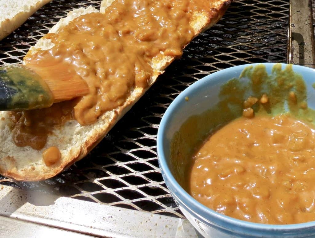A bowl of sauce and a loaf of French bread being spread with mustard barbecue sauce with a brush on the grill.