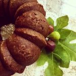 Fig cake on lace doily and fig leaves with fresh figs.