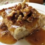 Bread Pudding With Pumpkin Pecan Praline Sauce on white plate.