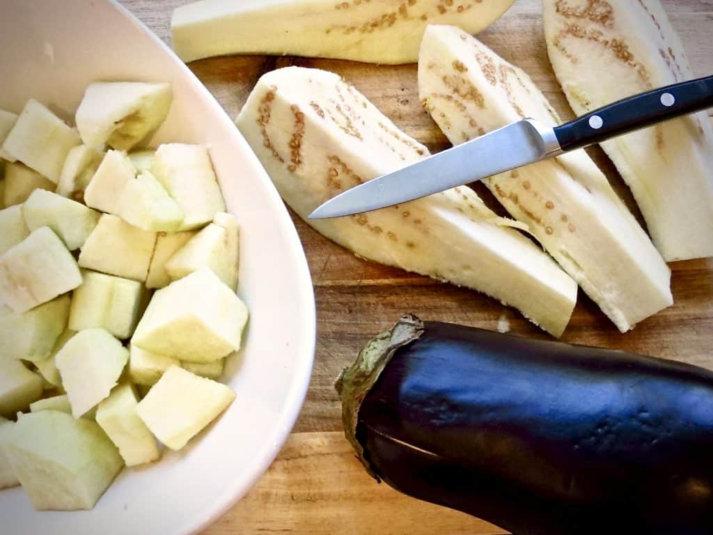 Cut up and whole eggplant on board and in white bowl.