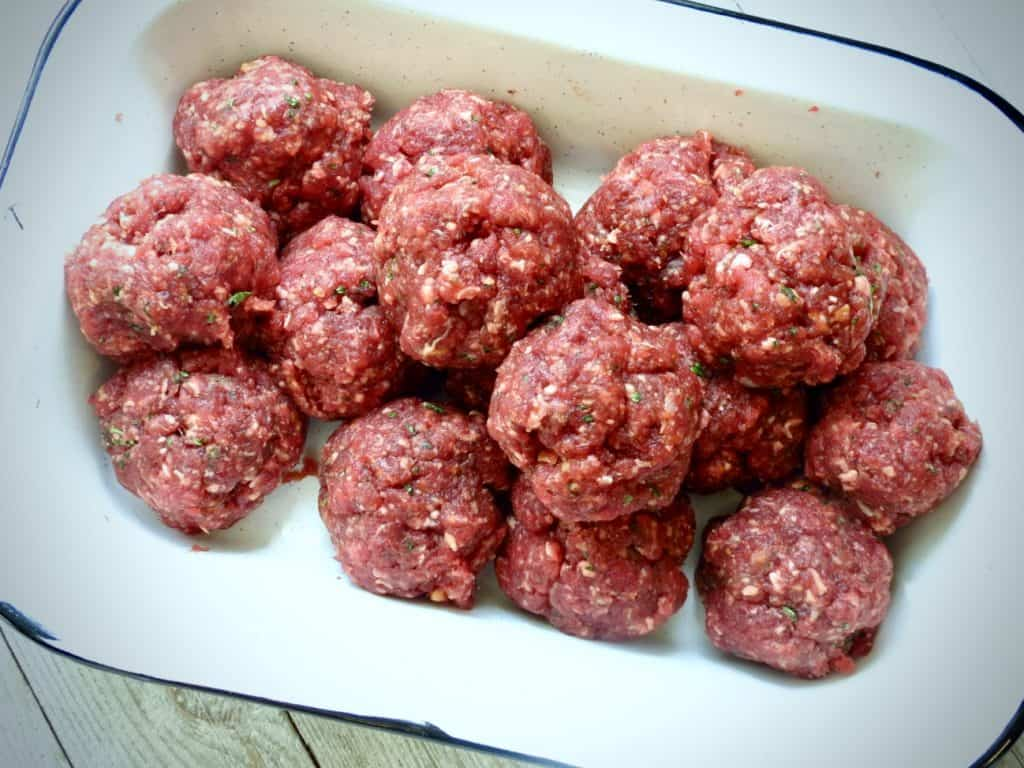 Rectangular dish of raw meatballs for Comforting Cajun Meatball Stew.
