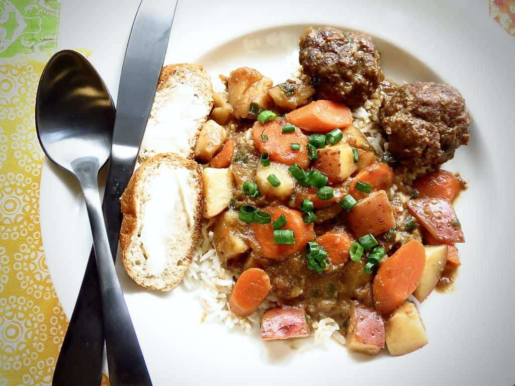 white plate of cajun meatball stew