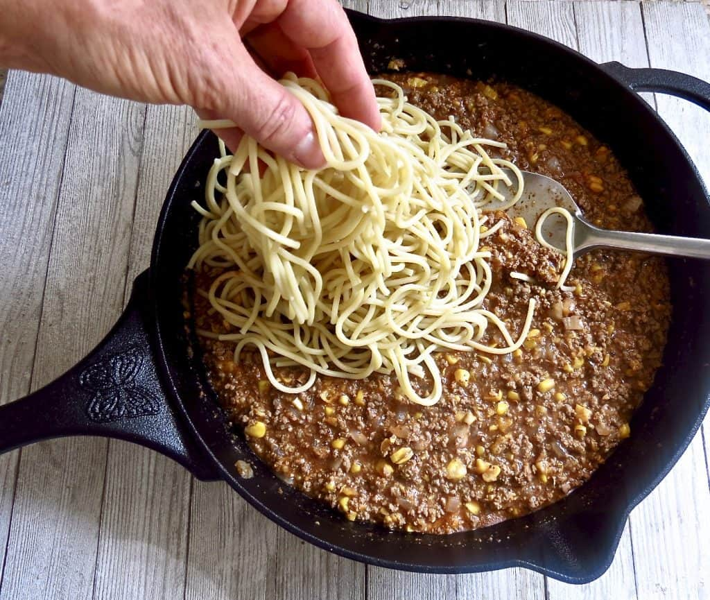 Spaghetti being added to cast iron skillet of ingredients for More Casserole, Cast Iron One-Pot Meal.