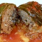 A cabbage roll cut in half sitting on a white plate in tomato sauce.