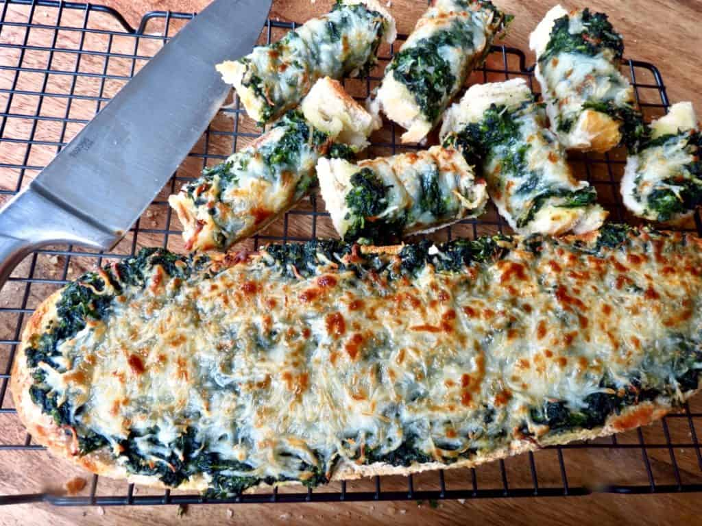 Loaf o spinach bread and cut up pieces on a rack with a knife.