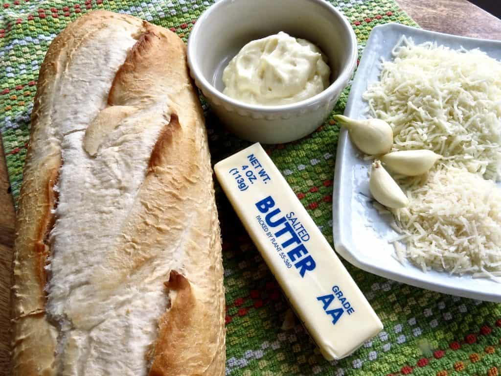 French bread loaf on a green dish towel with butter, mayonnaise in a bowl, garlic bulbs, and grated white cheeses.