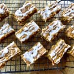 Pumpkin bars with glaze cooling on a rack.