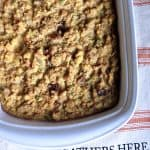 Cooked cornbread in a white casserole dish on an orange and white striped place mat.