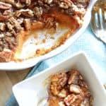 A casserole dish if Sweet Potato Casserole with a smaller dish with some sweet potato casserole in it.