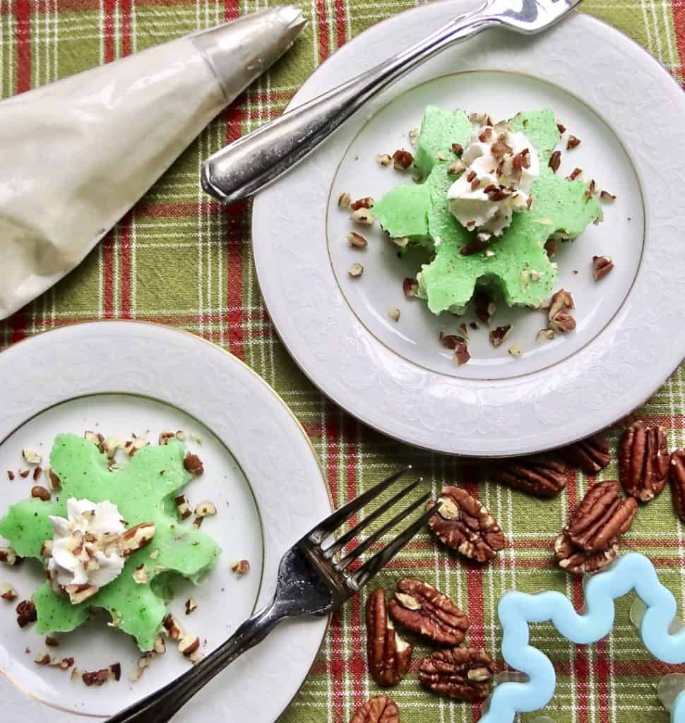 Two salad plates with snowflake cutouts of Congealed Salad, Cherry Or Lime Flavored.