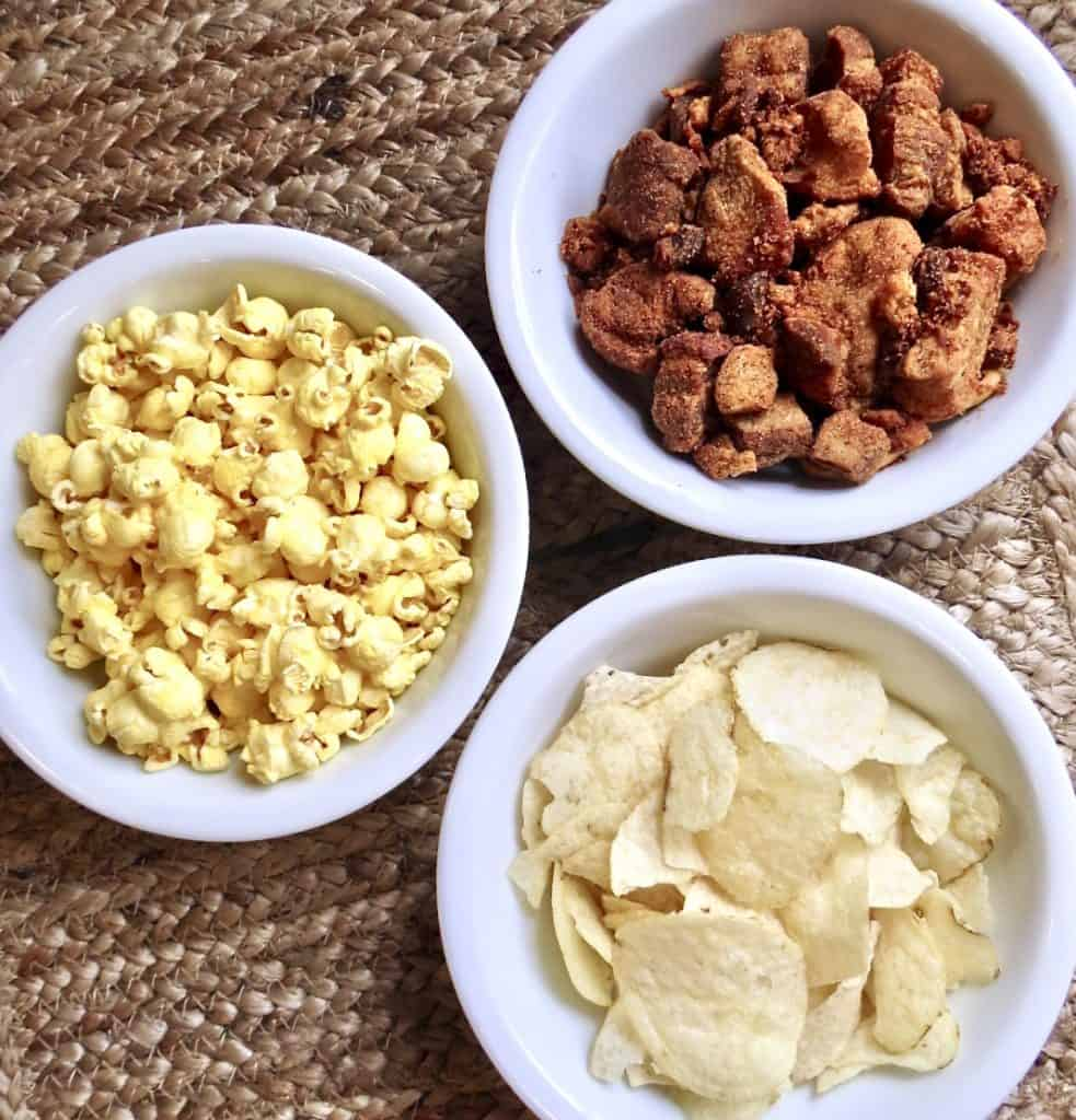 Three white bowls of potato chips, popcorn, and cracklings for Appetizers And Food Board.