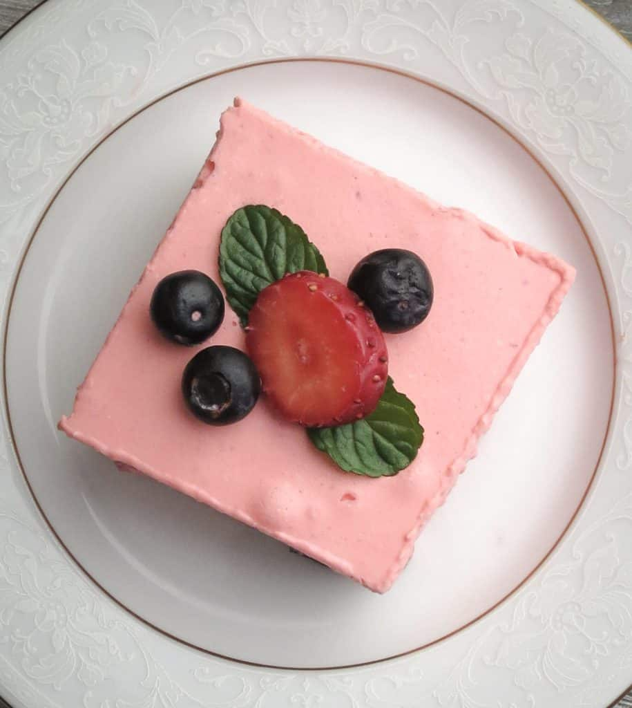 A white plate with a piece of Keto Strawberry Jello dessert on it and berries on top.