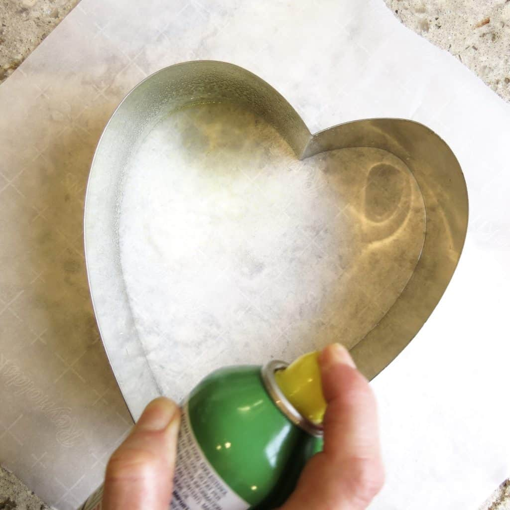 Spraying vegetable spray in a heart shaped tin mold for Valentine Candy Crunch.