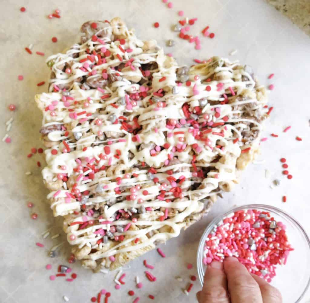Heart shape molded Valentine Candy Crunch topped with sprinkles.